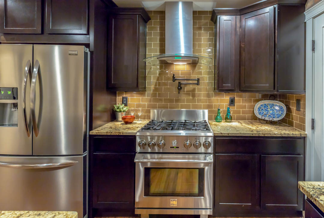 kitchen stove and oven with dark brown cabinets