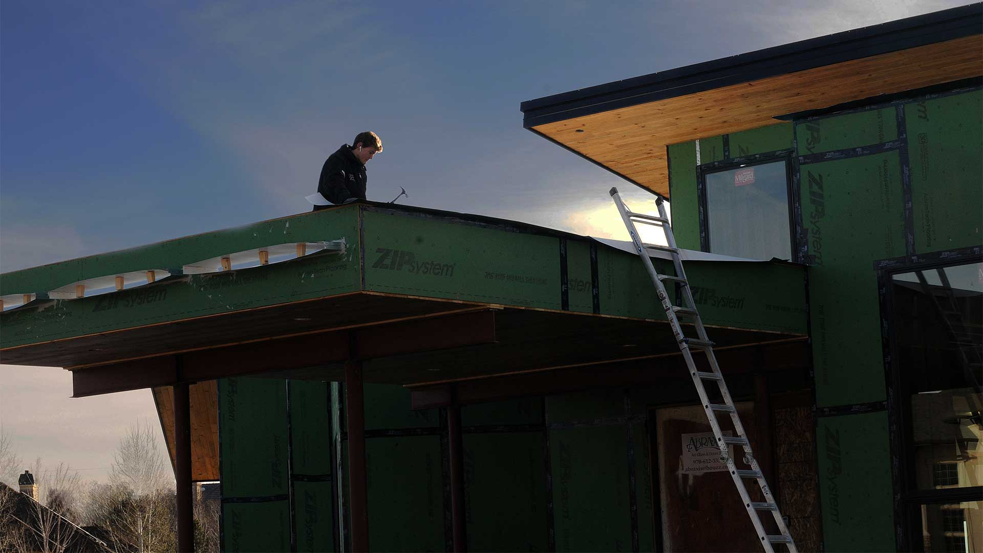 man working on roof of a new home